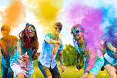 Cheerful and happy soiled friends throw bright paints on camera and smiling. Company of young people in sunglasses having fun with holi paints on spring summer festival. Holi party concept.