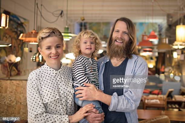 Happy owners standing with son at furniture store