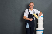 Smiling painter holding a paint roller and leaning on stack of paint bucket. Portrait of happy mature painter looking at camera isolated over grey wall. Satisfied handyman with roller and paint bucket