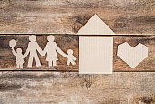 Happy paper family with house and heart cut out over wooden background