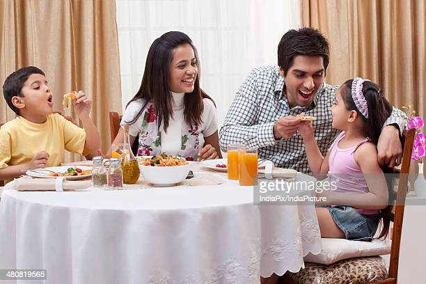 Happy parents and children having food at restaurant table