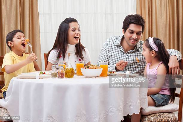 Happy parents and children having food together at restaurant table