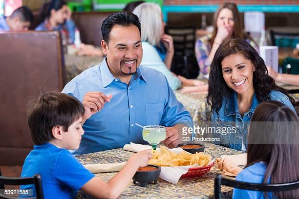 Happy parents having meal with children in Tex-Mex restaurant