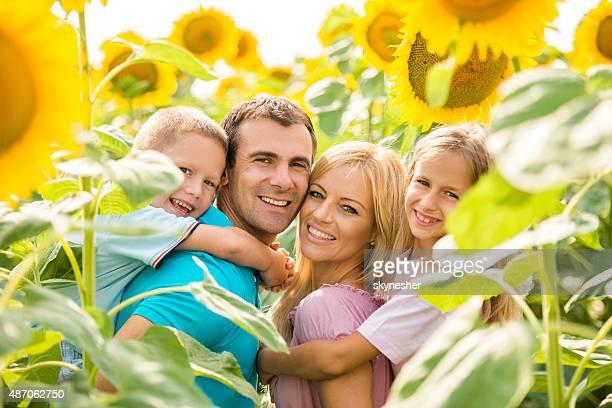 Felizes pais piggybacking as crianças entre sunflowers.
