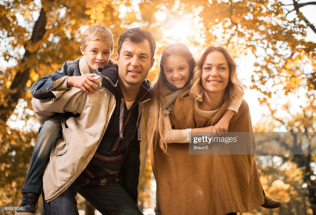 Happy parents piggybacking their children in the park. : Stock Photo
