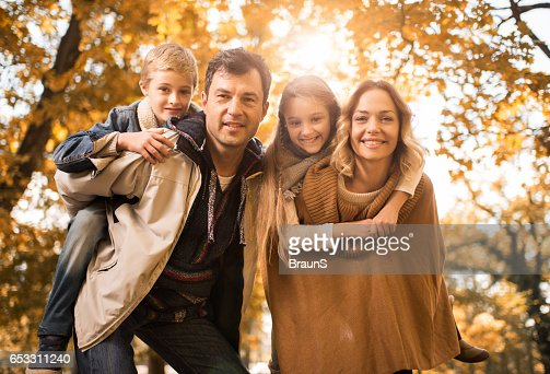 Happy parents piggybacking their children in the park. : Stock-Foto