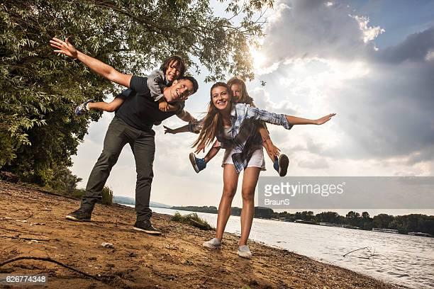 Happy parents piggybacking their children near the river.