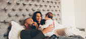 Happy parents playing with their newborn son on bed at home. Couple with little baby boy on bed.
