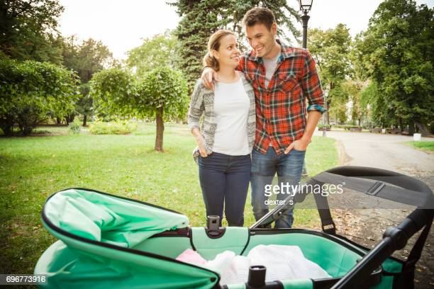 Happy parents standing behind stroller