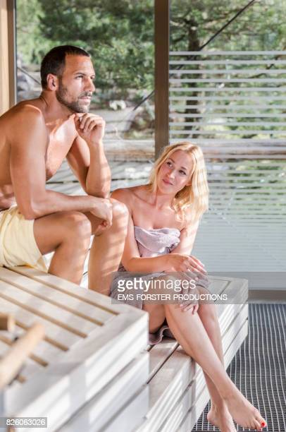 happy parents sweating in a wooden sauna enjoying and relaxing the day spa