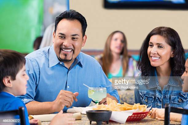 Happy parents talking to children during meal at restaurant