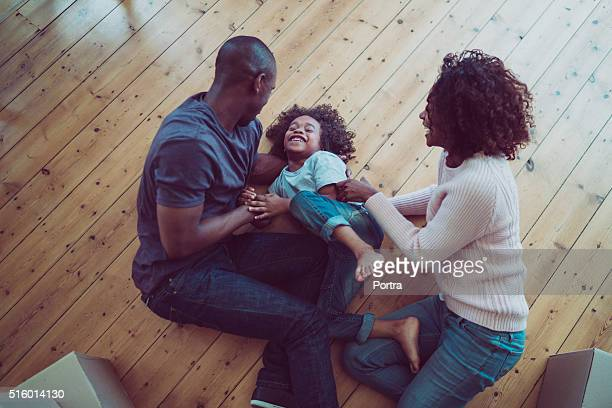 Happy parents tickling son on hardwood floor