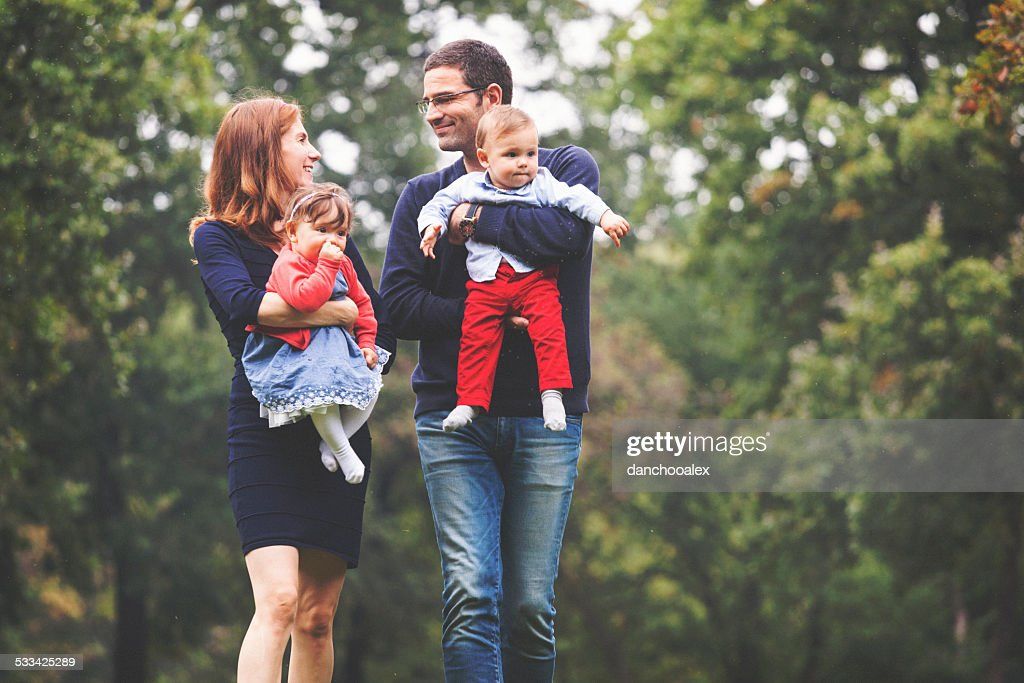 Happy parents walking in the park with twin babies : Stock Photo