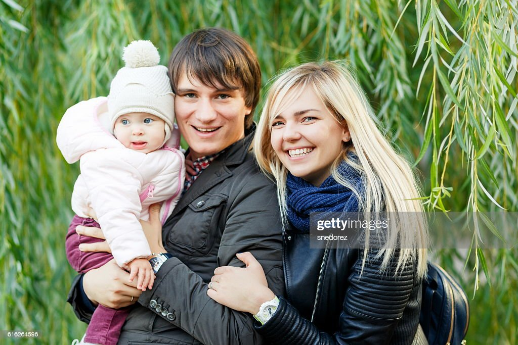 Happy parents with child standing near tree in park : Stock Photo
