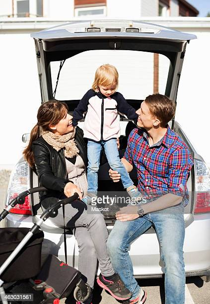 Happy parents with daughter and baby carriage sitting in car trunk