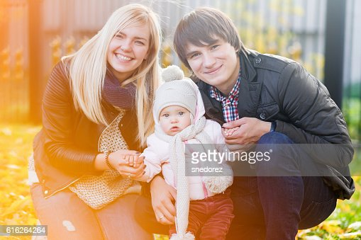 Happy parents with daughter in autumn park : Stock Photo