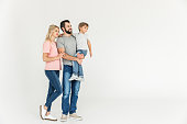 cute happy little boy with mother and father standing together and looking away isolated on white