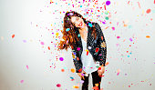 Happy young and beatiful woman with fashion leather jacket enjoying the party with confetti