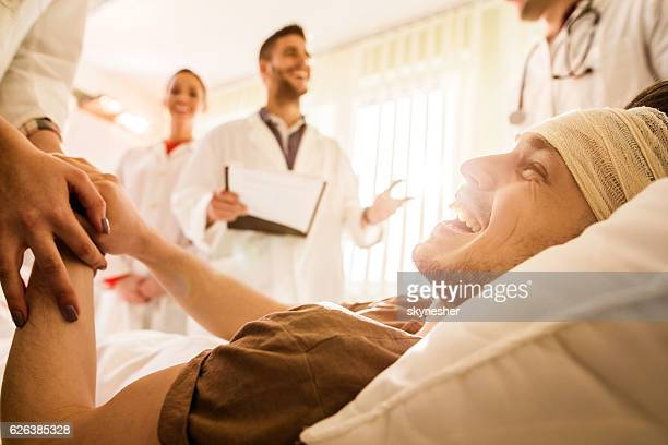 Happy patient holding hands with unrecognizable doctor at clinic.