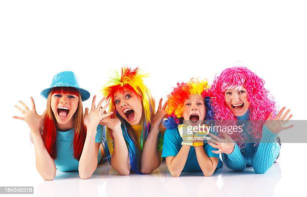 Happy people doing antics, wearing colorful wigs.