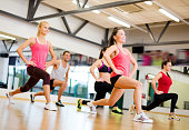 fitness, sport and healthy lifestyle concept - group of people exercising in gym.  Four women and one man are doing lunges.  They are all smiling and looking ahead.
