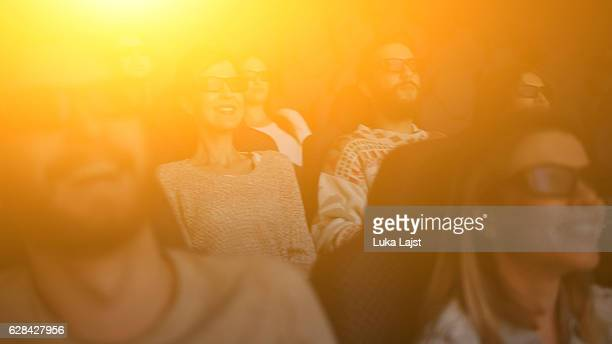 happy people enjoying in the cinema watching a 3d movie