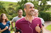 Portrait of a happy cheerful man listening to music while jogging. Man listening to music while jogging with group. Happy trainer in park running with team.'r