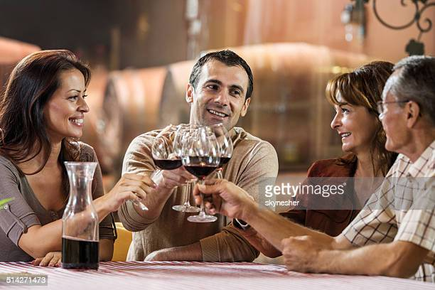Happy people toasting in a winery.