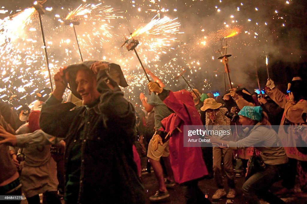 Happy people with fire and sparks in the celebration of the Correfocs of la Mercè Barcelona Catalonia