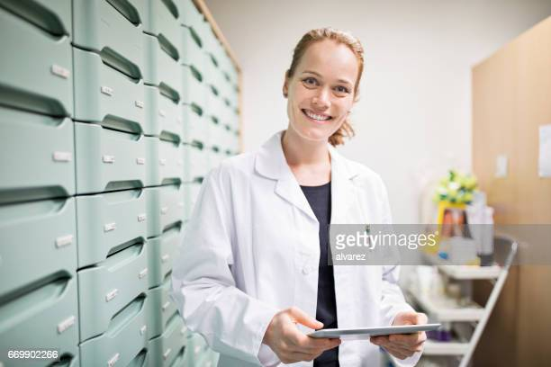 Happy pharmacist holding tablet pc in storage room