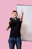 Happy photographer holding camera with thumbs up gesture over pink background
