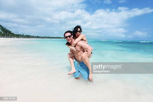 Feliz, divertida pareja divirtiéndose en la playa