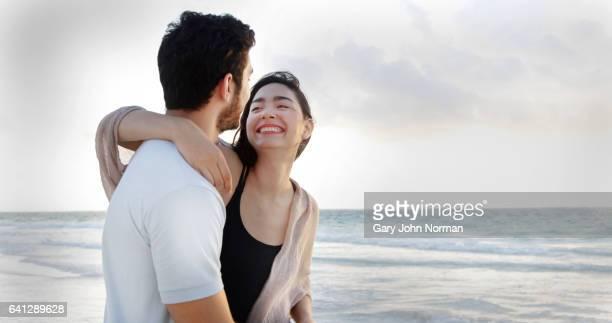 Happy, playful couple on beach walking beside the sea.