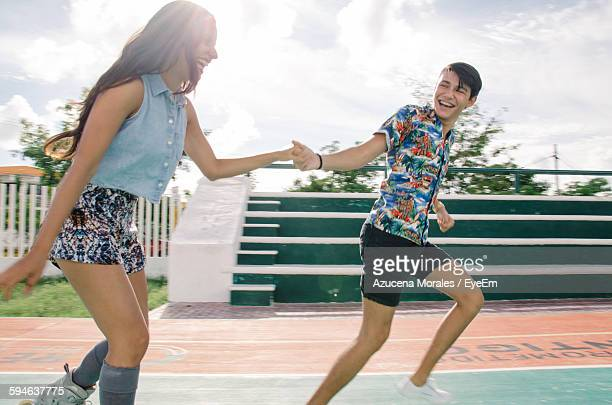 Happy Playful Friends Running On Racing Track Against Sky