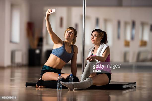 Happy pole dancers taking a selfie with mobile phone.