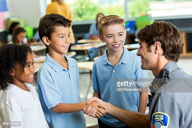 Happy police officer greets schoolchildren