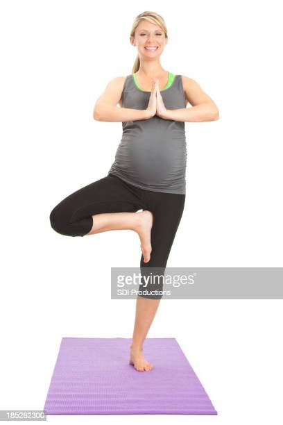 Happy pregnant balancing in yoga pose