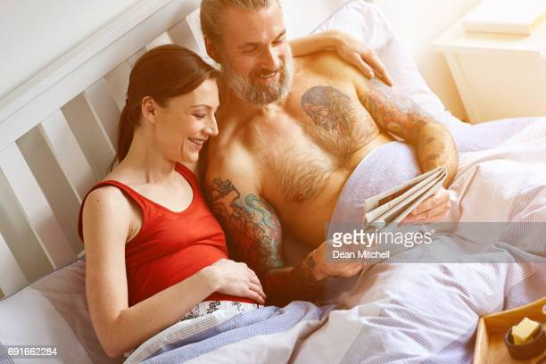 Happy pregnant  couple reading newspaper in bed
