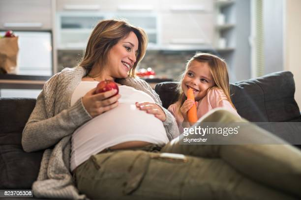 Happy pregnant mother and her small girl eating healthy food at home.