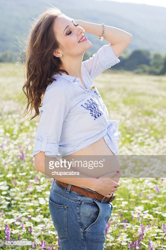 Happy pregnant woman in daisy flowers field : Stock Photo