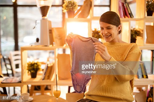 Happy pregnant woman looking at baby clothes in a cafe.
