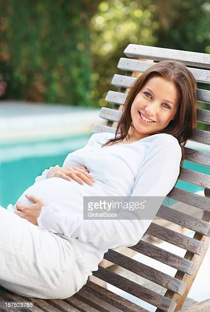 Happy pregnant woman on a recliner