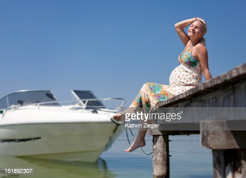 happy pregnant woman relaxing on jetty : Stock Photo