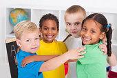 group of happy preschool kids hugging in classroom