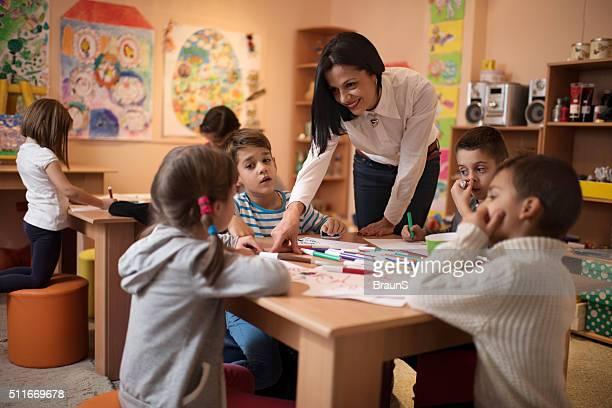 Glückliche Kinder mit Lehrer helfen Kindern, ihre Zeichnungen.