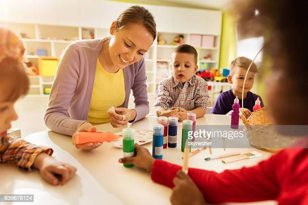 Happy preschool teacher coloring with kids in kindergarten.