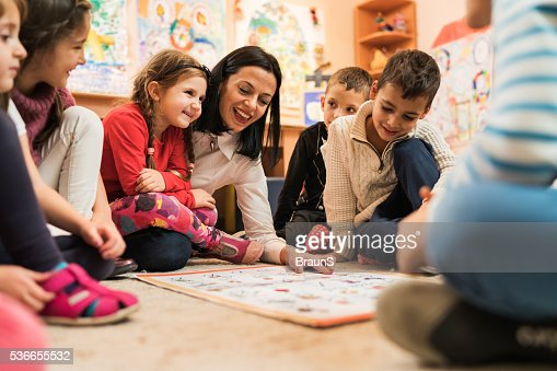 Happy preschool teacher educating large group of children in kindergarten.