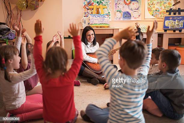 Happy preschool teacher playing a guitar on music lesson.
