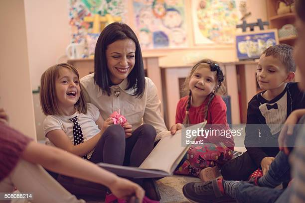Happy preschool teacher telling stories to group of kids.