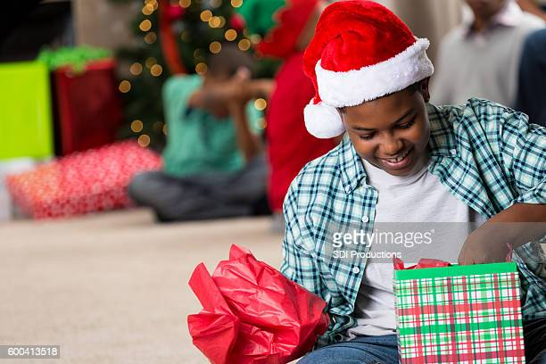 Happy preteen African American boy opening a Christmas gift
